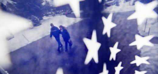A couple is seen through an American flag as they walk to a polling place for the New Hampshire primary, Tuesday, Feb. 9, 2016, in Nashua, N.H.